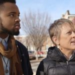 Younger Black Man and Older White Woman standing together looking off into the distance